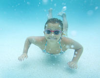 Child swimming underwater in an outdoor pool Stock Images