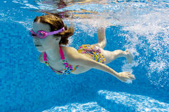 Child swimming underwater in pool Stock Photos