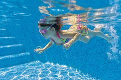 Child swimming underwater in pool Royalty Free Stock Images