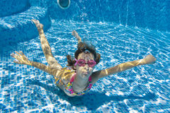 Child swimming underwater in pool Stock Image