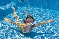 Child swimming underwater in pool Stock Image