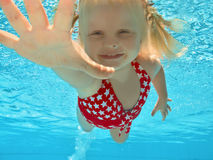 Child swimming underwater in pool. Young girl swimming underwater in pool Stock Images
