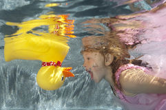 Child swimming underwater withi toy duck Royalty Free Stock Images