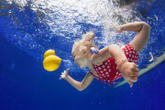 Child swimming underwater for yellow lemon in the blue pool Royalty Free Stock Photography