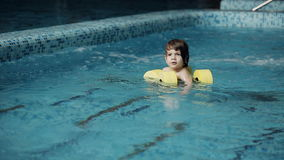 Child swims in the pool. Little boy swimming in the pool at the leisure center stock video footage