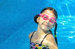 Child swims in pool under water, funny happy girl in goggles has fun and makes bubbles, kid sport Stock Photo