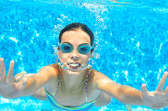Child swims in pool underwater, funny happy girl in goggles has fun under water and makes bubbles, kid sport Royalty Free Stock Photos