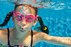 Child swims in pool underwater, funny happy girl in goggles has fun under water and makes bubbles, kid sport Royalty Free Stock Image