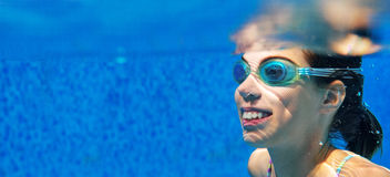Child swims in pool underwater, girl in goggles has fun Stock Photography