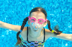 Child swims in pool underwater, girl in goggles has fun under water and makes bubbles Royalty Free Stock Image