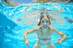 Child swims in pool underwater, girl has fun in water. Child swims in pool underwater, happy active girl has fun in water, kid sport on family vacation Royalty Free Stock Image