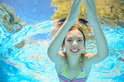 Child swims in pool underwater, girl has fun in water. Child swims in pool underwater, happy active girl has fun in water, kid sport on family vacation Royalty Free Stock Photo