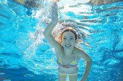 Child swims in pool underwater, girl has fun in water Royalty Free Stock Photos