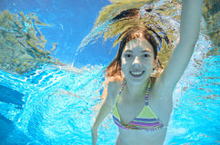 Child swims in pool underwater, girl has fun in water Royalty Free Stock Photo
