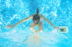 Child swims in pool underwater, girl has fun in water. Child swims in pool underwater, happy active girl has fun in water, kid sport on family vacation Royalty Free Stock Photography