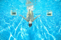 Child swims in pool underwater, girl has fun in water. Child swims in pool underwater, happy active girl has fun in water, kid sport on family vacation Royalty Free Stock Images
