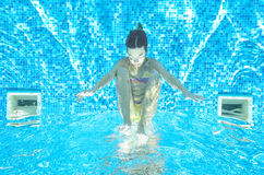 Child swims in pool underwater, girl has fun in water. Child swims in pool underwater, happy active girl has fun in water, kid sport on family vacation Stock Photography