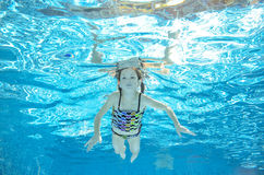 Child swims in pool underwater, girl has fun in water. Child swims in pool underwater, happy active girl has fun in water, kid sport on family vacation Royalty Free Stock Photos