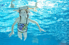 Child swims in pool underwater, girl has fun in water Royalty Free Stock Images