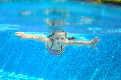 Child swims in pool underwater, girl has fun in water. Child swims in pool underwater, happy active girl has fun in water, kid sport on family vacation Stock Photos