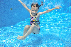 Child swims in pool underwater, girl has fun in water Stock Image