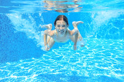 Child swims in pool underwater, girl has fun in water. Child swims in pool underwater, happy active girl has fun in water, kid sport on family vacation Stock Images