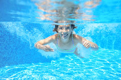 Child swims in pool underwater, girl has fun in water. Child swims in pool underwater, happy active girl has fun in water, kid sport on family vacation Stock Photo