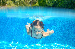 Child swims in pool underwater, girl has fun in water Stock Photo