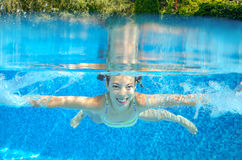 Child swims in pool underwater, girl has fun in water. Child swims in pool underwater, happy active girl has fun in water, kid sport on family vacation Stock Image