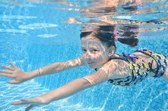 Child swims in pool underwater, happy girl dives and has fun under water, kid fitness and sport on family vacation royalty free stock photo
