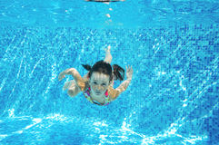 Child swims in pool underwater, happy active girl dives and has fun under water, kid fitness and sport Royalty Free Stock Photo
