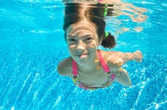 Child swims in pool underwater, happy active girl dives and has fun under water, kid fitness and sport Royalty Free Stock Images