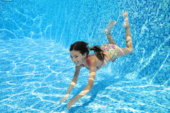 Child swims in pool underwater, happy active girl dives and has fun under water, kid fitness and sport Royalty Free Stock Photography