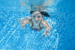 Child swims in pool underwater, happy active girl dives and has fun under water, kid fitness and sport. On family vacation Stock Photography