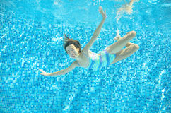 Child swims in pool underwater, happy active girl dives and has fun under water, kid sport Royalty Free Stock Images
