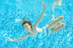 Child swims in pool underwater, happy active girl dives and has fun under water, kid sport Stock Photos