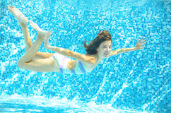 Child swims in pool underwater, happy active girl dives and has fun under water, kid sport Royalty Free Stock Photos
