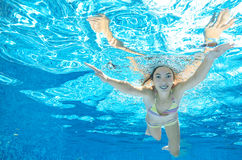 Child swims in pool underwater, happy active girl dives and has fun under water, kid sport Stock Photo