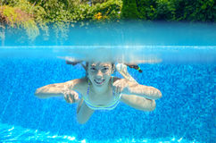 Child swims in pool underwater, happy active girl has fun. Under water, kid sport on family vacation Stock Image