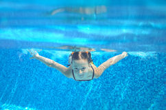 Child swims in pool underwater, happy active girl has fun. Under water, kid sport on family vacation Royalty Free Stock Photography