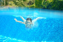 Child swims in pool underwater, happy active girl has fun. Under water, kid sport on family vacation Royalty Free Stock Photos