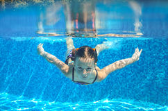 Child swims in pool underwater, happy active girl has fun. Under water, kid sport on family vacation Royalty Free Stock Image