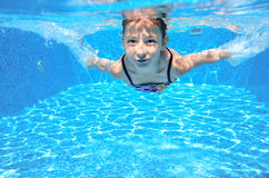 Child swims in pool underwater, happy active girl has fun Stock Images