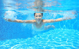 Child swims in pool underwater, happy active girl has fun. Under water, kid sport on family vacation Stock Photo