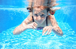 Child swims in pool underwater, happy active girl has fun Royalty Free Stock Photos