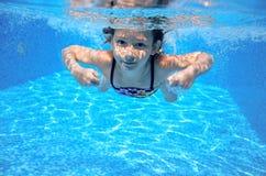 Child swims in pool underwater, happy active girl has fun Stock Photo