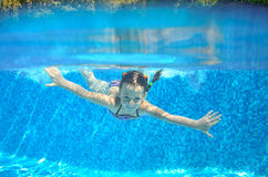 Child swims in pool underwater, happy active girl has fun Royalty Free Stock Photo