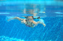 Child swims in pool underwater, happy active girl has fun. Under water, kid sport on family vacation Royalty Free Stock Images
