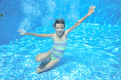 Child swims in pool underwater, happy active girl has fun under water, kid sport Stock Photography
