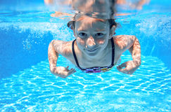 Child swims in pool underwater, happy active girl has fun under water, kid sport. On family vacation royalty free stock photography
